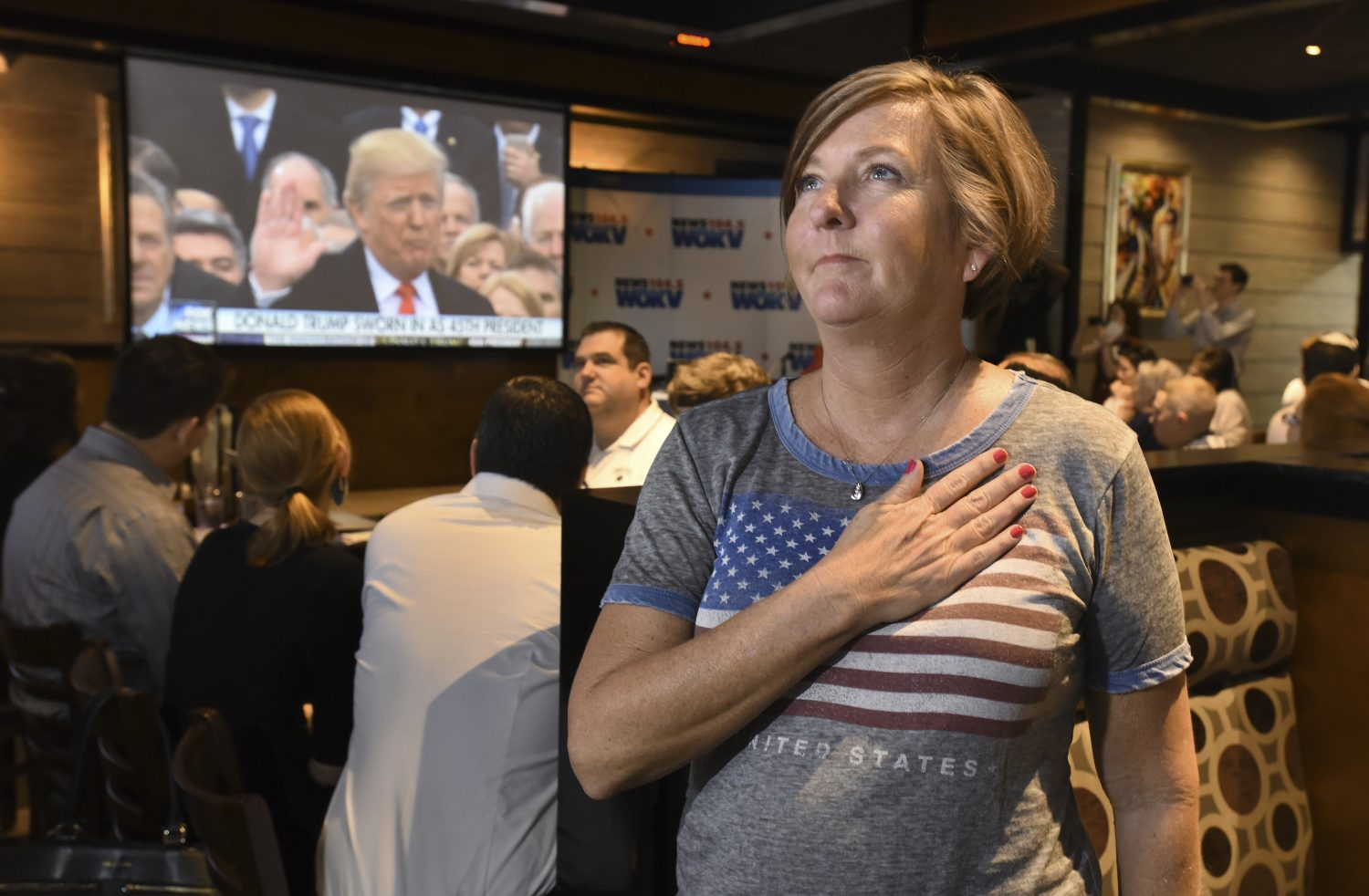 Victoria Barette from Jacksonville, Fla., holds her hand over her heart as she and other patrons watch Donald Trump take the presidential oath of office on the multiple video screens during an Inauguration Watch Party at Whiskey Jax in Marsh Landing, Fla., Friday, 20. 2017. (Bob Self/The Florida Times-Union via AP)