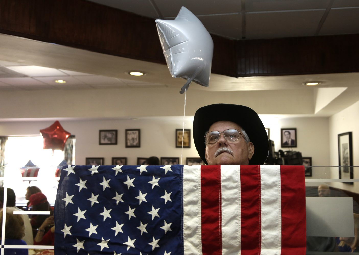 Cuban American Rene Espinosa watches a televised broadcast of the presidential inauguration of Donald Trump, Friday, Jan. 20, 2017, during a watch party organized by Hispanas for Trump, in Miami. (AP Photo/Lynne Sladky)