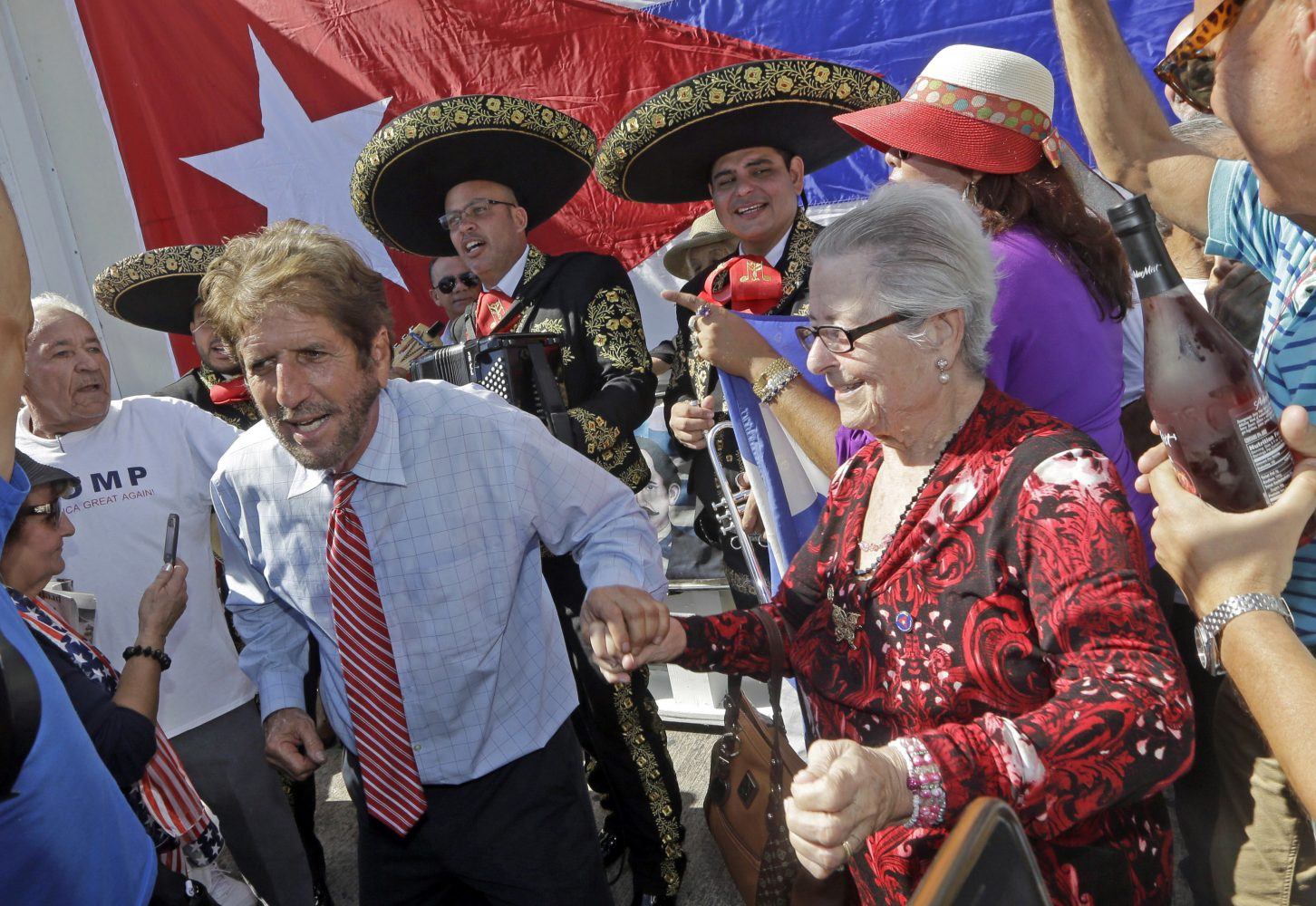 Cuban-American Miguel Saavedra, left, dances to the music of a mariachi group as they celebrate, Friday, Jan. 20, 2017, in the Little Havana area in Miami, before President-elect Donald Trump is sworn in as the 45th president of the United States. (AP Photo/Alan Diaz)