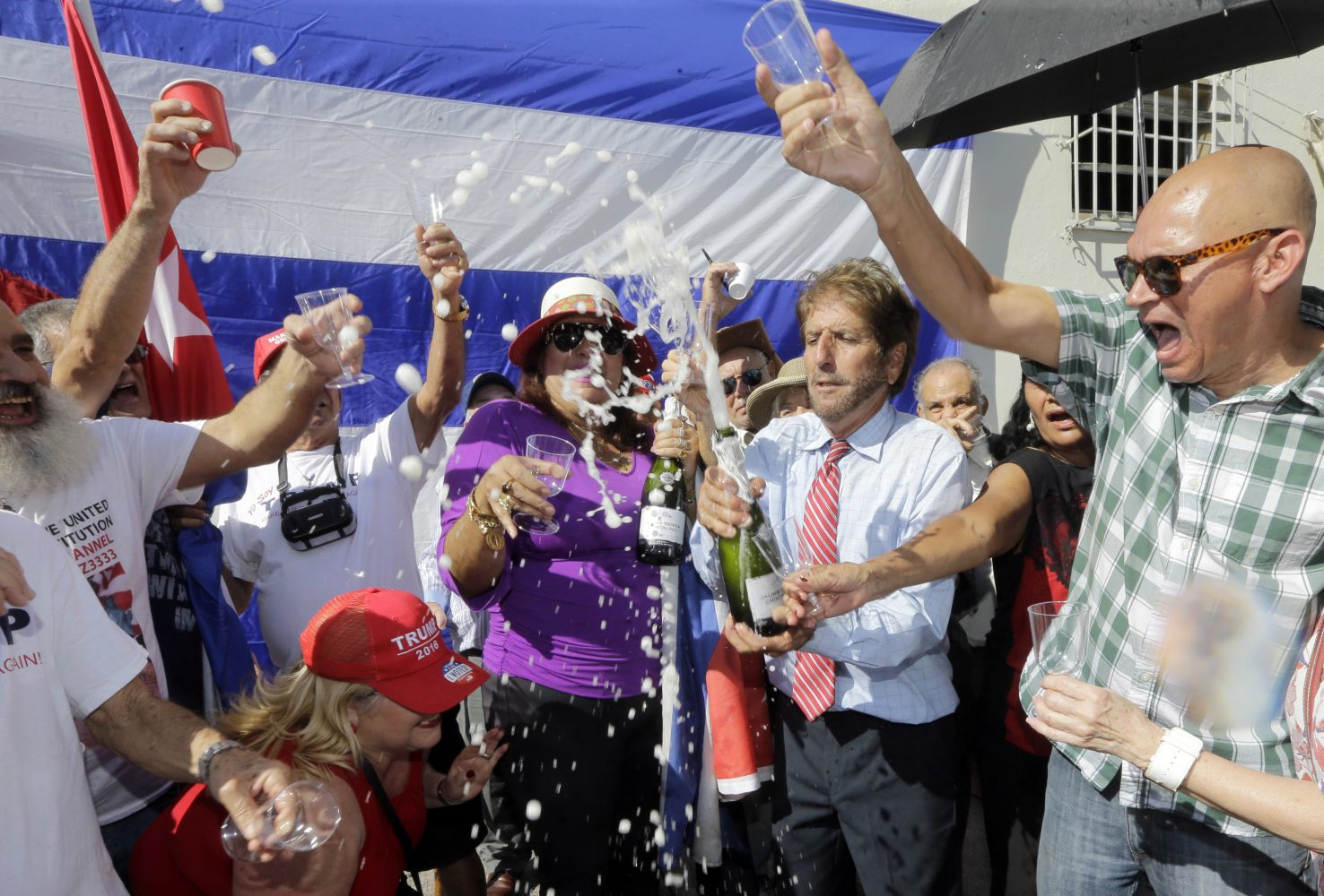 Cuban-American Miguel Saavedra pops a bottle of champagne as they celebrate Friday, Jan. 20, 2017, in the Little Havana area in Miami, before President-elect Donald Trump is sworn in as the 45th president of the United States. (AP Photo/Alan Diaz)