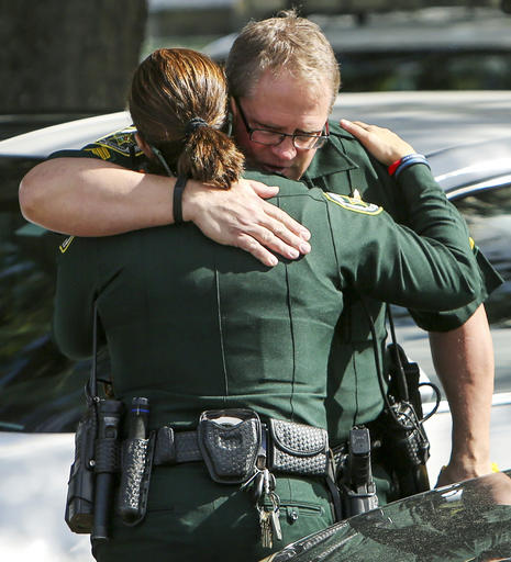 Law enforcement officers hug as other officers, not seen, escort the body of the Orange County deputy that died in the line of duty on Monday to the Orange County Medical Examiner's Office on Monday, Jan. 9, 2017, in Orlando, Fla. The Orlando Police Department announced the death of Master Sgt. Debra Clayton on its official Twitter account Monday morning. (Jacob Langston/Orlando Sentinel via AP)