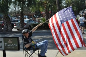 Mark Lawrence, 52, sits in a lawn chair at the shopping center entrance and waves a different version of the American flag. Instead of 50 white stars, Lawrence's flag is adorned with company logos to represent his view of who really runs the country. (Teal Garth/WUFT News)
