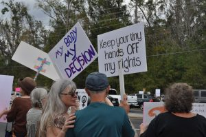 Crystal River resident Kent Barkhouse stands side by side with his daughter, Jody Neermann, flashing their double-sided signs to the street and fellow protesters behind them. Not pictured was Barkhouses' wife, Joey and their little dog, Mocha, who came out to support. (Teal Garth/WUFT News)