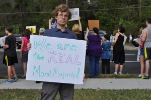 """Dana Vold, 29, holds his protest sign in front of the overcrowded sidewalk on Newberry Road. He explained that his sign referred to The Moral Majority political party of the 1980s. """"The real moral thing to do is to oppose this government,"""" he said."""
