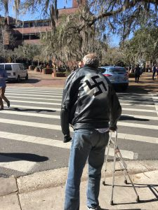 Roger Wiggins strolls on UF's campus wearing a jacket prominently featuring a Swastika. He said he didn't know that the Liberation Rally was going to take place today.