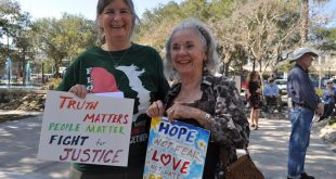 Kim Wheeler and Lonna Bear hold signs outside of Gainesville City Hall protesting Donald Trump's inauguration on Friday. Wheeler and Bear traveled from Williston and Cedar Key to participate in the protest (Ashleigh Braun/WUFT News)