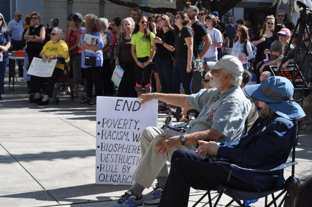 A group of protesters watches various speakers, poets and singers who preformed during the People's Inauguration Event outside of Gainesville City Hall on Friday. Some carry signs and are wearing clothing expressing their views (Ashleigh Braun/WUFT News)