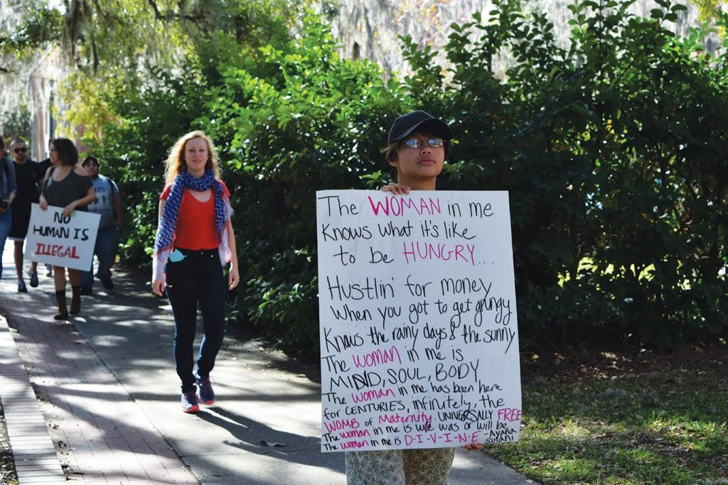DeeDee Barrito marches through Plaza of the Americas with a sign supporting female rights and gender equality during Friday's student walkout at the University of Florida (Cindy Lu/WUFT News)
