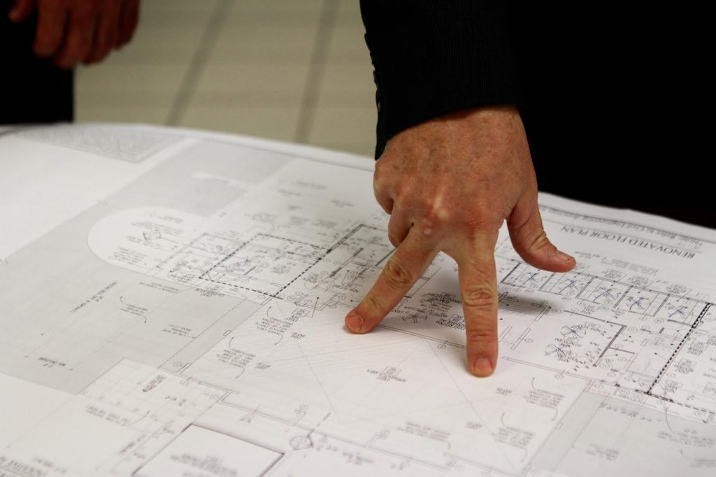 Newberry city manager Mike New points to the blueprints for the Newberry Fire Department's station renovations on Monday. The current layout has bunker-style sleeping quarters for four firefighters, 22-year-old tanker trunks and little storage space, he said. (Emma Green/ WUFT News)