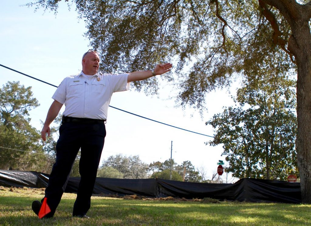 Newberry Fire Department Chief Ben Buckner points towards a spot in the yard of the station that will be renovated. The almost 40-year-old station is expanding to include more private bunking for firefighters and an ambulance bay, among other improvements. (Emma Green/ WUFT News)