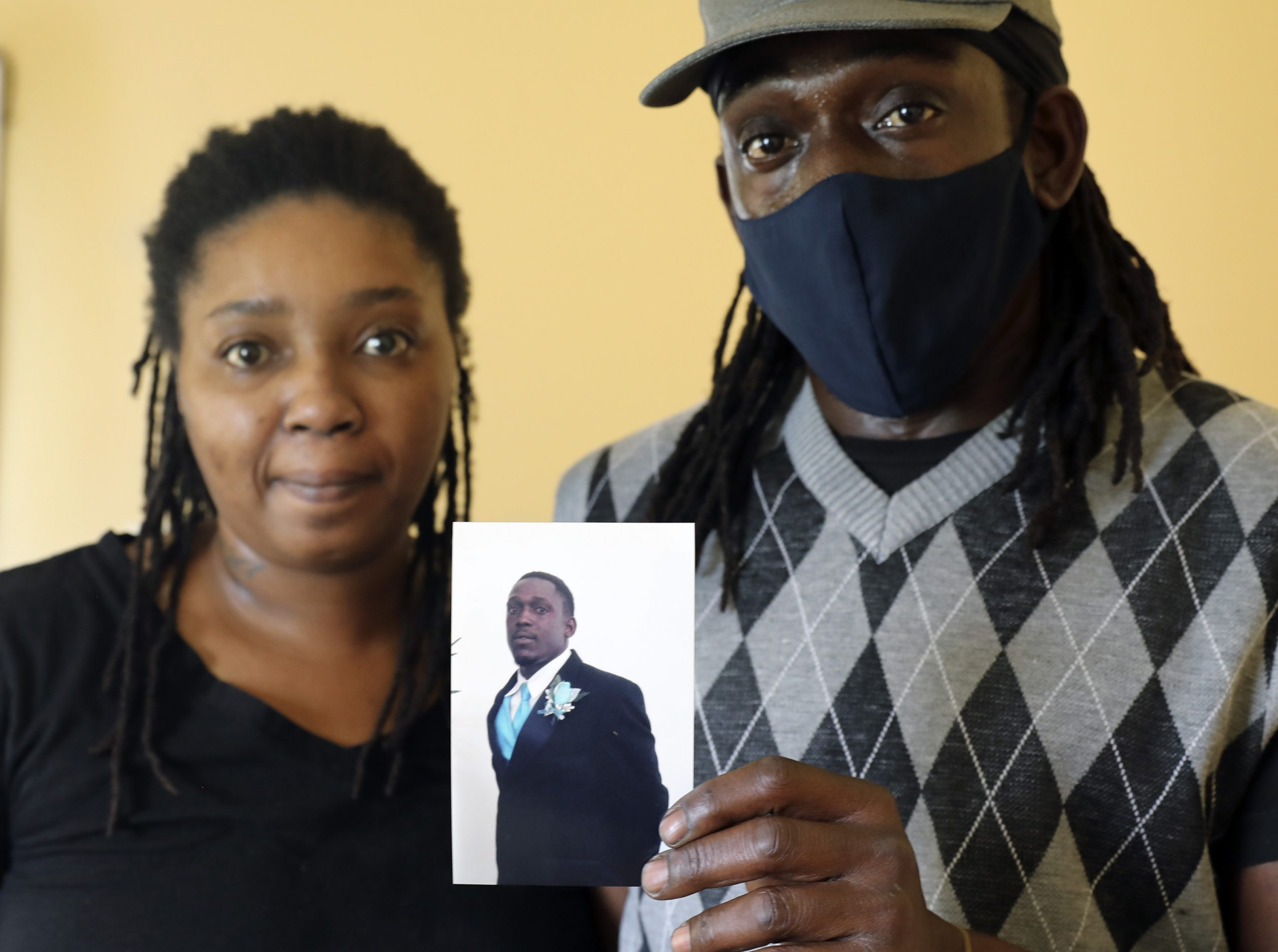 Reginald Jackson holds a photo of himself when he was younger, while standing with his wife, Ciara Jackson, in their Lakeland, Fla., home .