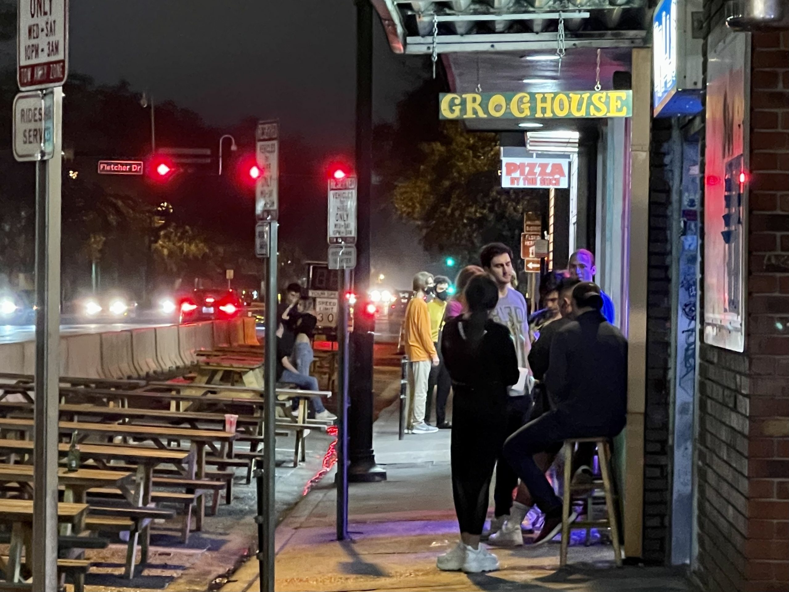 students without their masks on are lined up s line up outside Grog House Grill, a popular Midtown bar on University Avenue.