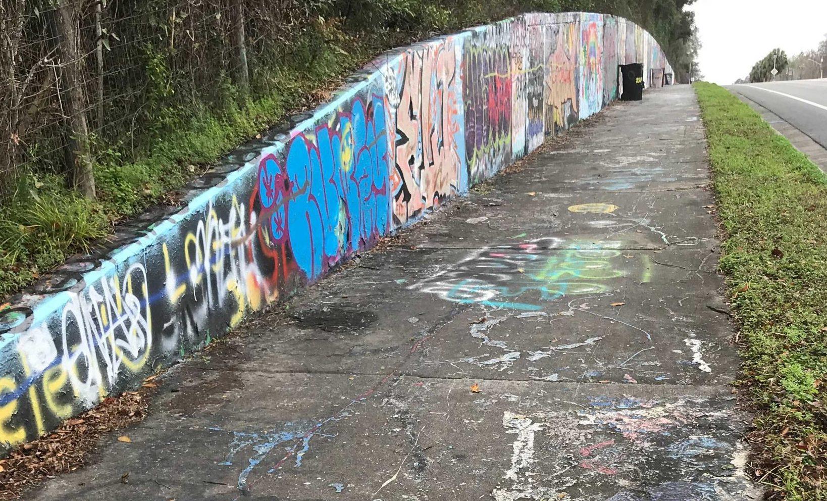Graffiti covers the sidewalk and walls of 34th street