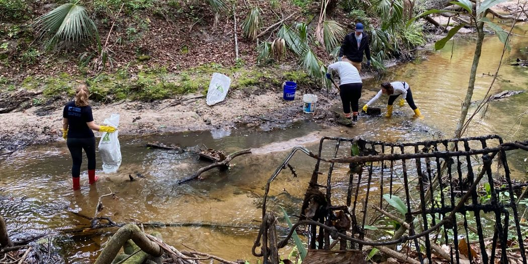 Four people stand in a creek with bags and tools for cleaning up.
