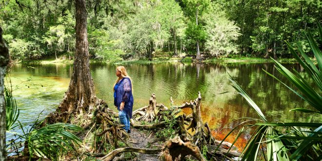 A woman stands by a body of water, surrounded by various trees and bushes.