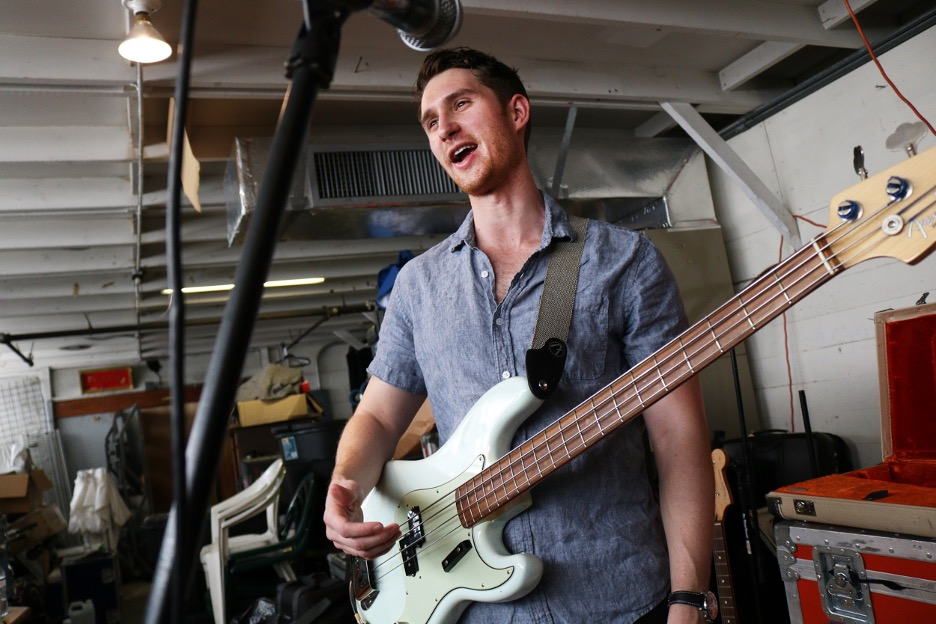 Bassist John Shermyen plays bass guitar in front of a microphone.