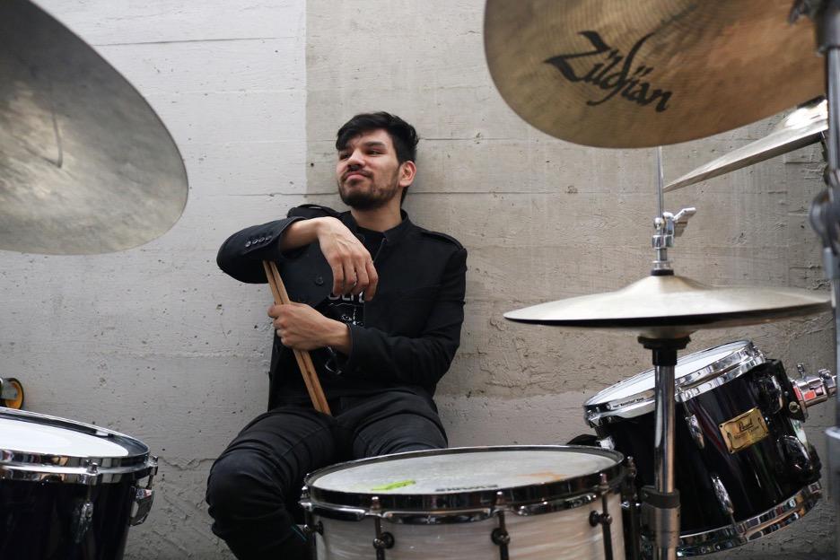 Drummer Alex Klausner sits in a room behind his drum set, holding a pair of drumsticks.