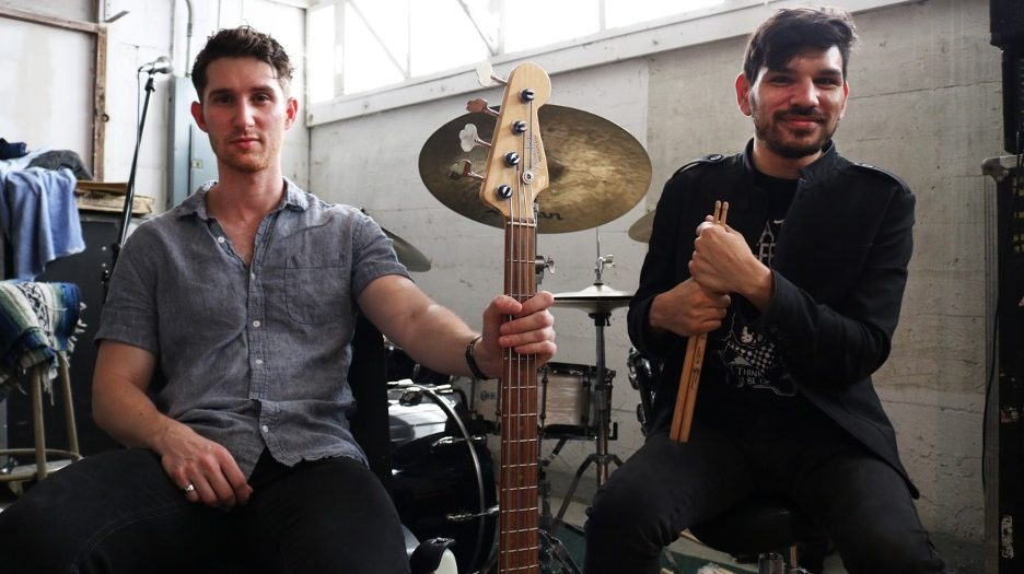 John Shermyen and Alex Klausner pose for a photo with their guitar and drum set.