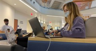 Female student wearing mask studying on computer in the J Wayne Reitz Union on the UF campus