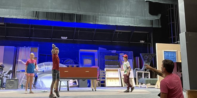 Three children are standing on a stage while the director is guiding their movements from the audience section.
