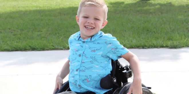 Jacen Macil, a 5-year-old boy from Ocala, is seen sitting on his wheelchair outdoors.
