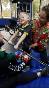 Jacen Smith is pictured centered holding onto an exercise bar with his two arms as a physical therapist is holding him from behind for support. Jacen is seen smiling.
