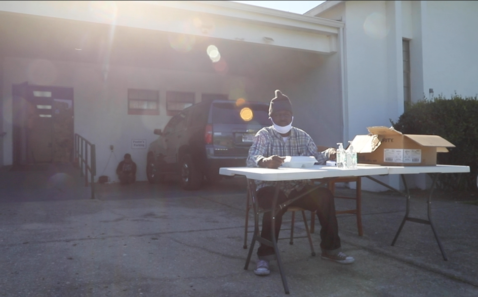 Marlin Johnson sits at a table outside the church.