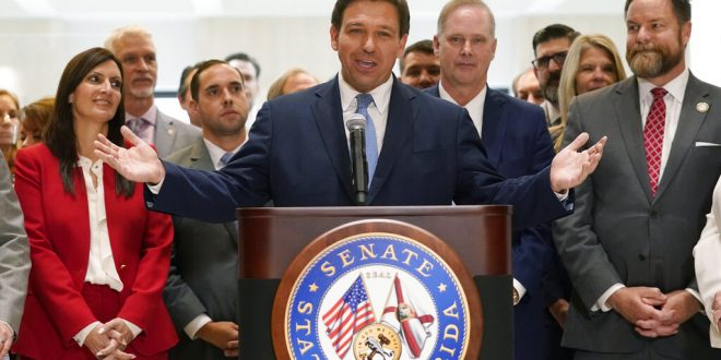 Florida Republican Governor Ron DeSantis speaks to a crowd with open arms.