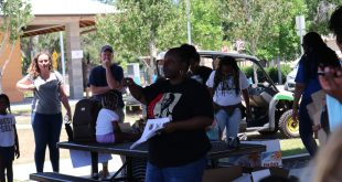 Yvette Carter explains the rules and guidelines for the children's scavenger hunt in the middle of a large crowd.