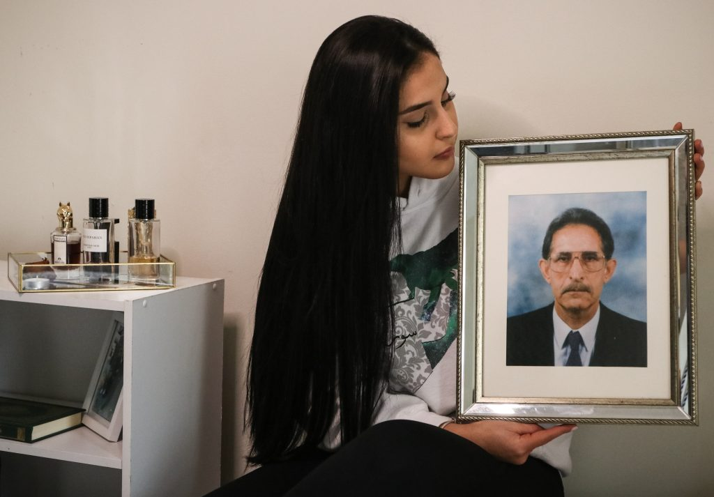 A young woman, in a sweatshirt with the outline of Syria on it, stares down at a photograph she is holding of an older man in a suit and tie and glasses. Her nightstand is next to her.