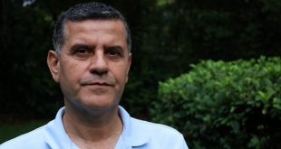 An middle-aged man stares solemnly into camera, wearing a light blue polo shirt.