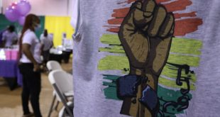 A t-shirt shows a brown fist held up against stripes of red, yellow and green, the shackles around the wrist breaking. In the background, balloons and people can be seen.