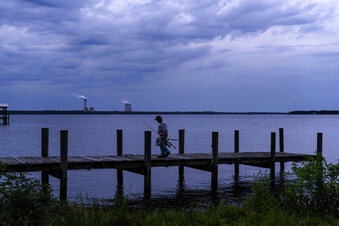 A fisherman walks along a dock on the St. Johns River as a coal-fired power plant stands in the background, in Palatka, Fla., Wednesday, April 14, 2021. After months in a prison cell, Warren Williams longed to fish the St. Johns again. He looked forward to spending days outdoors in his landscaping job, and to writing poems and music in his free time.
