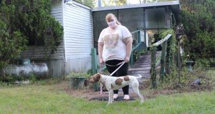 Woman and her dog stand outside of their mold-infested home.